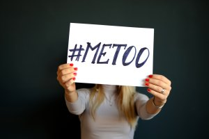 Young blonde woman holding up a #MeToo placquard in front of her face